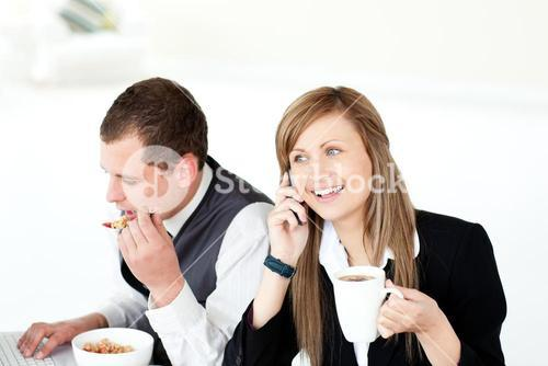 Charming businesswoman drinking coffee while her husband eating cornflakes