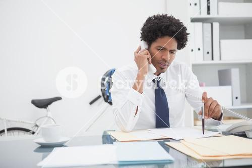 Serious businessman on the phone at desk