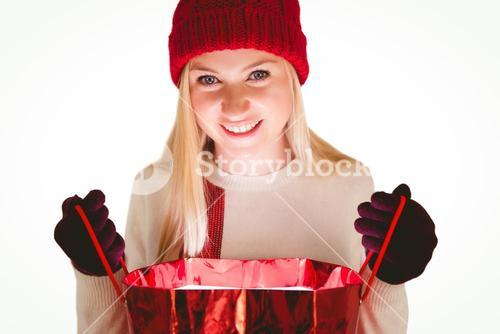 Festive blonde opening a gift bag