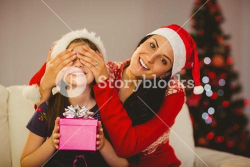 Mother surprising her daughter with christmas gift