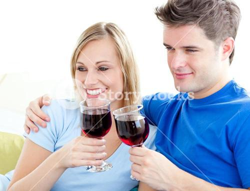Affectionate couple drinking wine sitting on a sofa in the livingroom