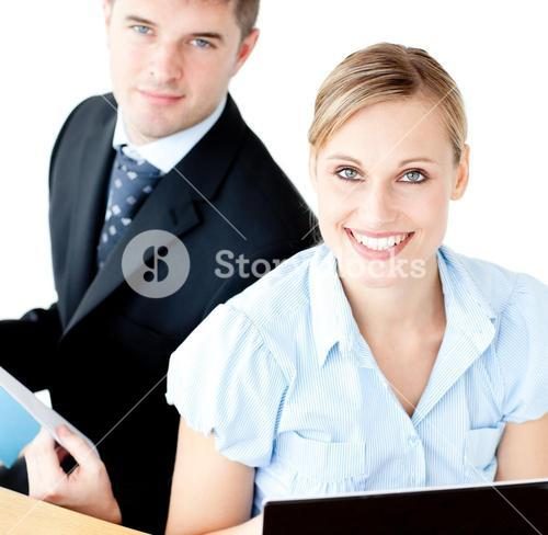 Beautiful couple of businesspeople smiling at camera using laptop