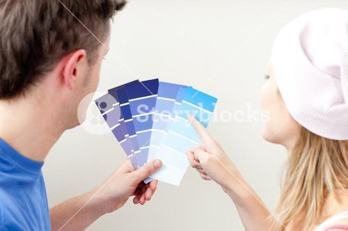 Concentrated young couple choosing color for a room