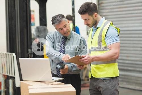 Workers scanning package in warehouse