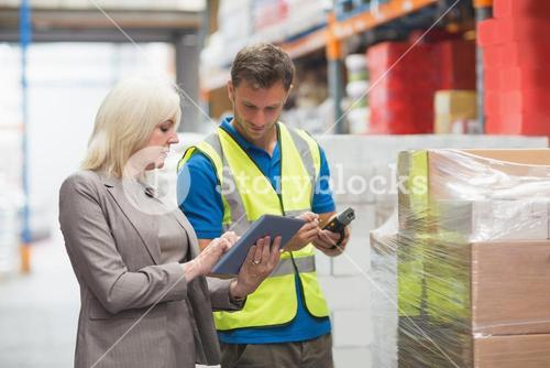 Manager using tablet while worker scanning package