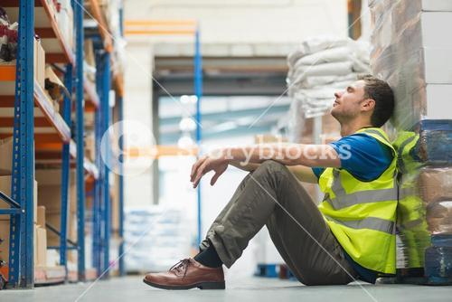 Tired manual worker sitting on floor