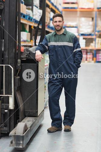 Manual worker leaning against the forklift