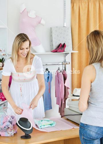 Positive saleswoman packing clothes in a bag