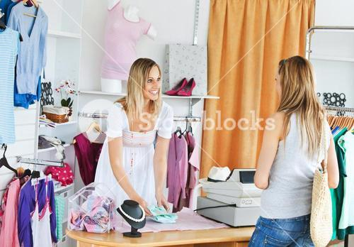Attractive saleswoman packing clothes in a bag