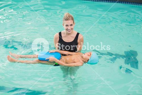 Cute little boy learning to swim with coach