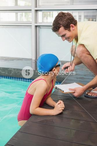 Swimming coach showing time to little girl