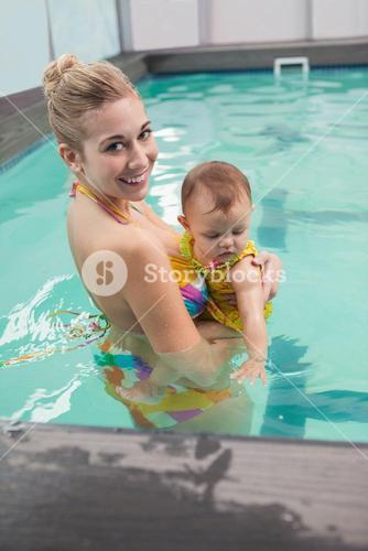 Pretty mother and baby at the swimming pool