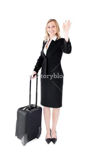 Delighted young businesswoman waving at the camera holding a suitcase