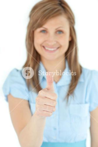 Radiant businesswoman smiling at the camera with thumb up