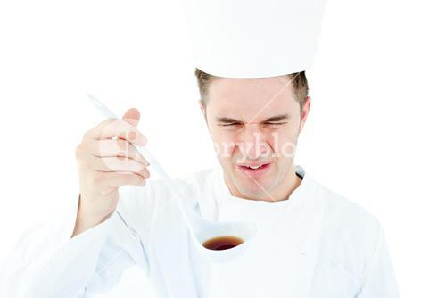 Young male chef tasting a soup with distorted face