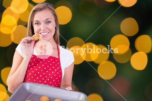 Composite image of pretty homemaker showing hot cookies
