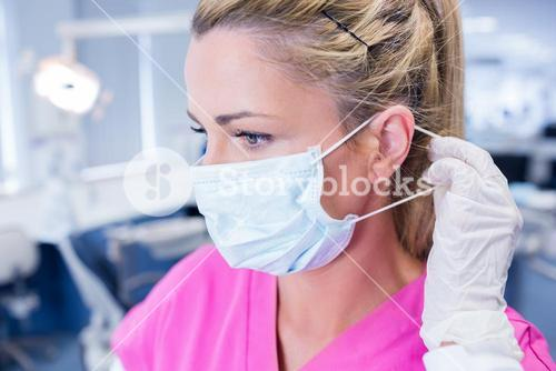 Dentist putting on her surgical mask