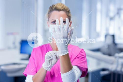 Dentist in pink scrubs putting on surgical gloves