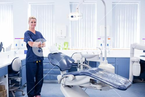 Dentist in blue scrubs standing with arms crossed beside chair