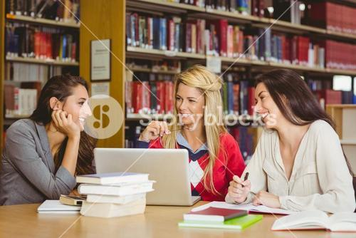 Smiling mature student with classmates using laptop