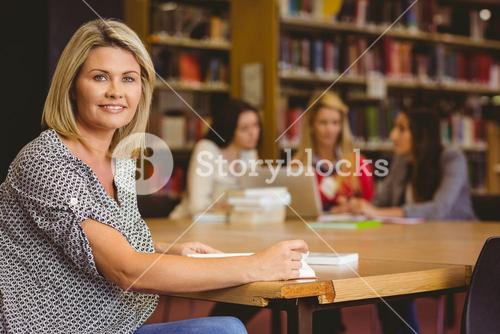 Smiling mature student studying at desk