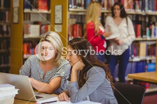 Two focused students on laptop with classmates behind them