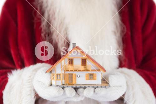 Santa holds a tiny house in his hands