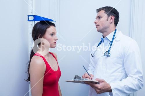 Confident doctor measuring patients height