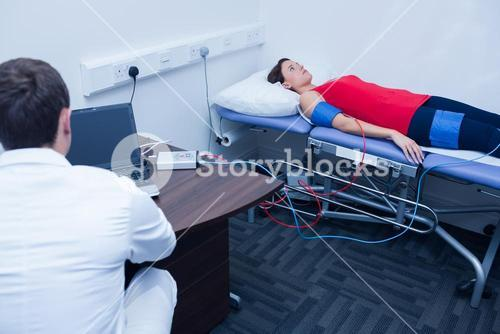 Doctor checking blood pressure of woman