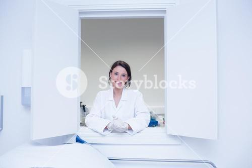 Female biologist smiling at the camera out the window