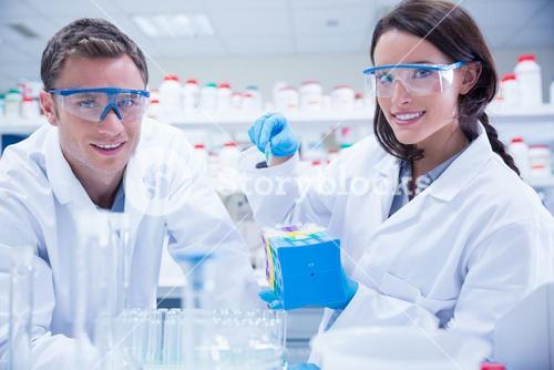 Smiling chemists working together looking at camera