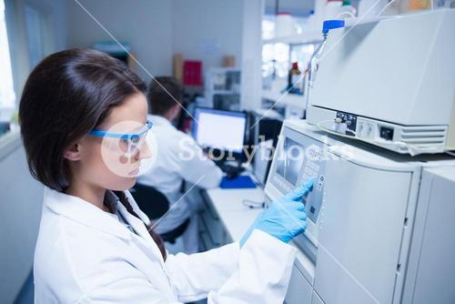 Young chemist using the machine