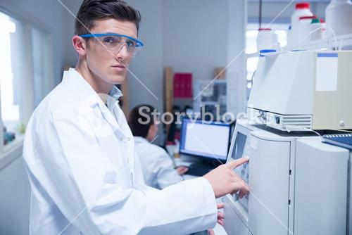 Unsmiling young chemist using the machine
