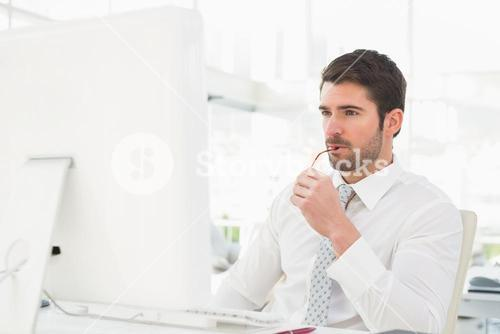 Serious businessman using computer monitor