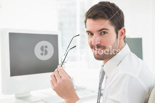 Happy businessman holding his glasses
