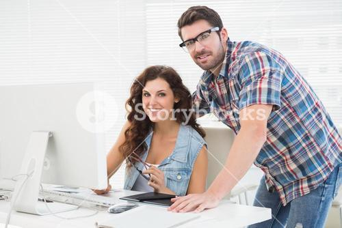 Smiling partners using computer together