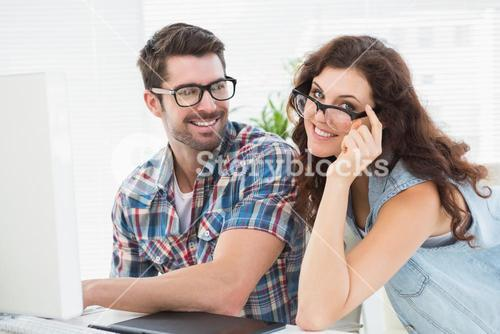 Happy coworkers with glasses posing