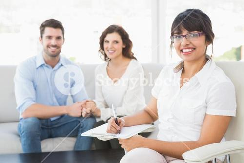 Smiling therapist with patients looking at camera