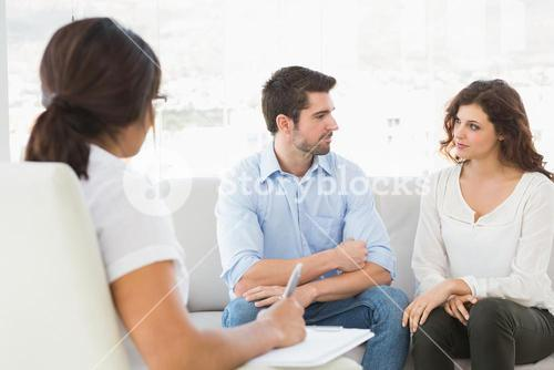 Couple sitting on sofa talking with their therapist
