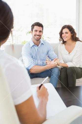 Reconciled couple smiling on couch