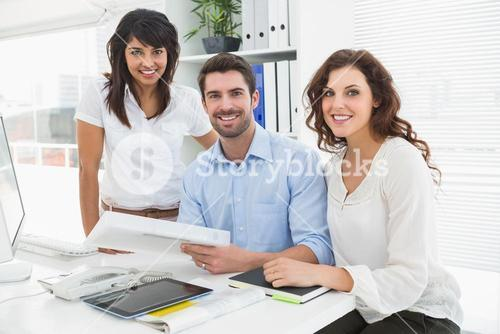 Smiling coworkers working together at desk