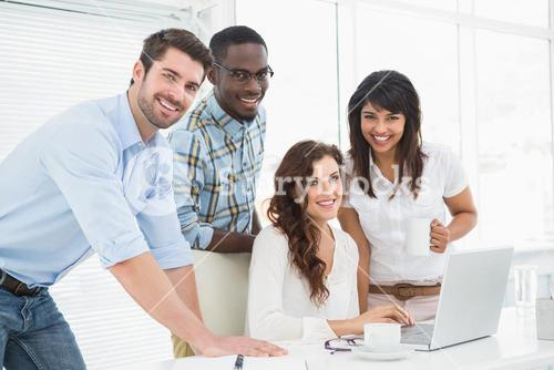 Happy coworkers working together with laptop