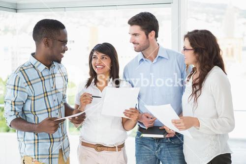 Smiling coworkers with files briefing together