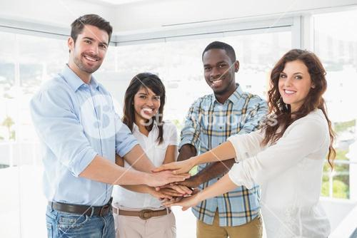 Happy coworkers joining hands in a circle