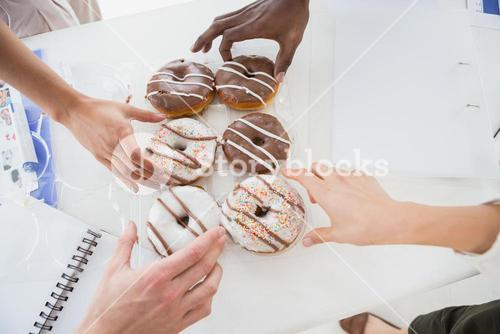 Business people taking doughnut at desk