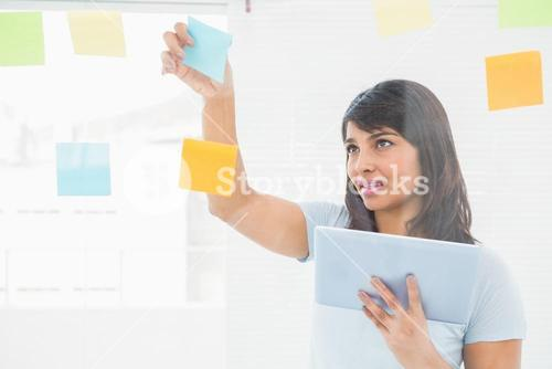 Businesswoman holding digital tablet and sticky notes