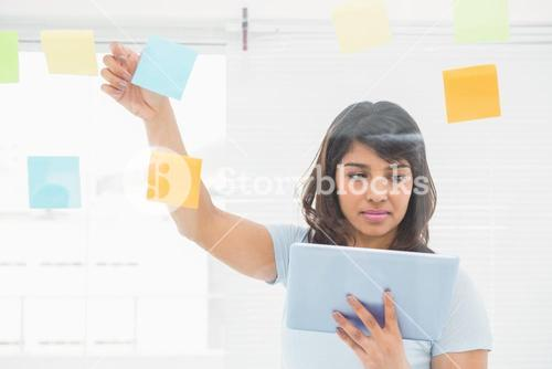 Concentrated businesswoman using tablet pc