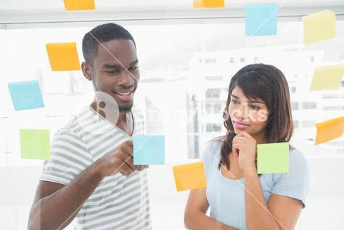 Smiling coworker reading sticky notes