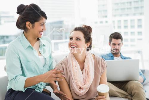 Smiling businesswomen chatting together on couch