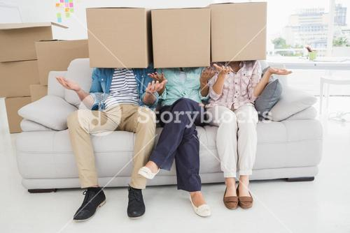 Colleagues covering with cardboard box gesturing